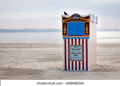 WEYMOUTH, UK - MAY 24th, 2019: A red and white striped wooden punch and Judy booth on a beach located in Weymouth, Dorset UK.