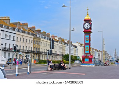 Weymouth,Dorset / England - 6/24/2019: The Jubilee Clock Tower on the Esplanade commemorating the Golden jubilee of Queen Victoria in 1888.Grade II Listed. Row of terraced houses with iron balconies.