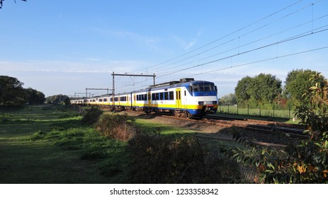 Wezep / Netherlands - October 11 2018: A Dutch modern NS sprinter train (type SGMm) passing some grassfields near by the railway station of Zwolle