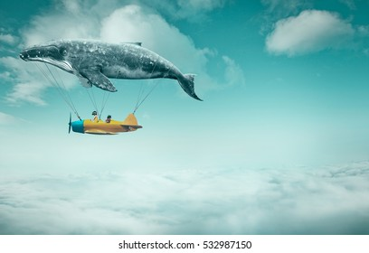 Whale floats in the air above the clouds carrying children in a yellow airplane. travel concept.