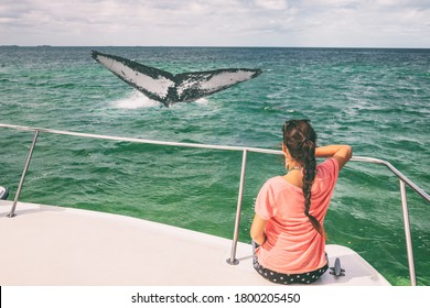 Whale watching boat tour tourist woman relaxing looking at humpback breaching flapping tail travel destination, summer vacation on deck of catamaran.