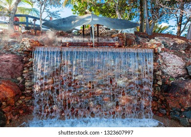 Whales tail fountainwith water cascading over autumnal colours