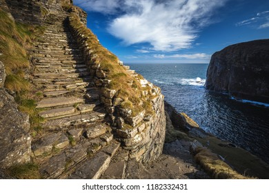 Whaligoe steps - steep stony stairs leads all the way down to the small beach below high cliffs near Whaligoe village, Highlands of Scotland.