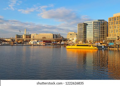 The Wharf, boat and skyline of buildings at the newly redeveloped Southwest Waterfront area of Washington, DC viewed from the water in fall with the Washington Monument in the background