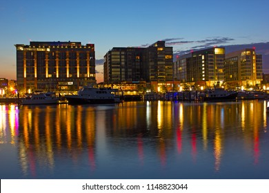 The Wharf district residential buildings with marina at dawn. The Wharf of Washington DC with waterfront and its colorful reflection in Potomac River.