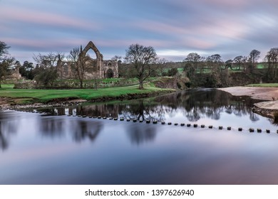 Wharfedale, Yorkshire Dales National Park, North Yorkshire, England, Britain, April 2016, ruins of Bolton Abbey (Priory) and stepping stones crossing River Wharfe