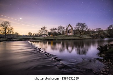 Wharfedale, Yorkshire Dales National Park, North Yorkshire, England, Britain, March 2017, ruins of Bolton Abbey (Priory) and stepping stones crossing River Wharfe at night with starry sky