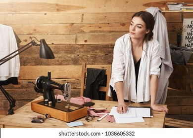 What a beautiful day to create something extraordinary. Portrait caucasian designer working in workshop, leaning on table while looking aside with dreamy expression, standing near sewing machine