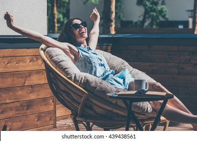 What a beautiful day! Beautiful young woman relaxing in a big comfortable chair on her outdoor house terrace