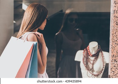 What a beautiful necklace! Rear view of beautiful young woman carrying shopping bags and looking through the window of fashion store