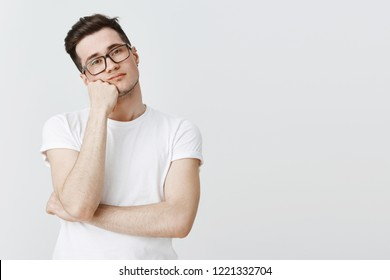 What boring day at work. Portrait of indifferent apathic and unintersted attractive young man in glasses leaning head on hand from boredom looking at camera with no interest and joy over grey wall