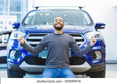 What a car! Happy handsome African man looking excited standing on his knees in front of his newly bought cool car expression emotions emotional winner victory winning arms raised victorious concept