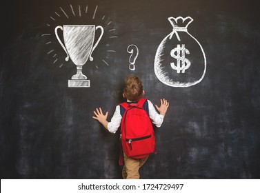What to chose - money or glory. Question for school boy. Big bag with money and win cup