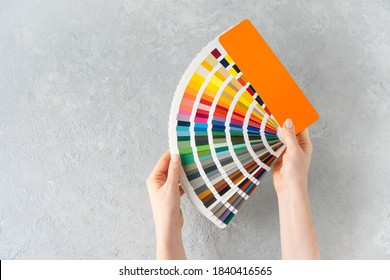 What color to paint the walls concept. Female hands holding a guide colors palette fan on a concrete background. Copy space.