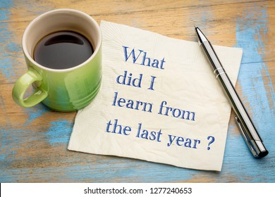 What did I  learn from the last year? Handwriting on a napkin with a cup of espresso coffee