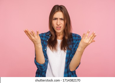 What do you want? Portrait of annoyed girl in checkered shirt raising arms in questioning gesture, saying I don't understand problem, looking indignant. indoor studio shot isolated on pink background