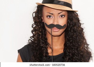 What do you think about my mustache? Portrait of playful young African woman in funky hat holding fake mustache on her face and looking at camera while standing against white background
