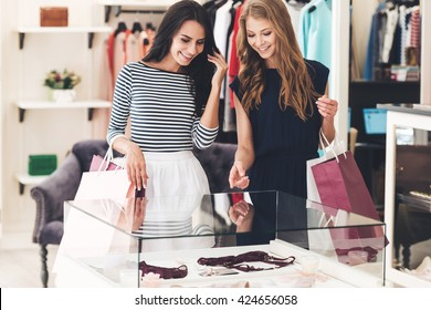 What do you think about this? Two beautiful women with shopping bags looking at lingerie showcase with smile while standing at the store