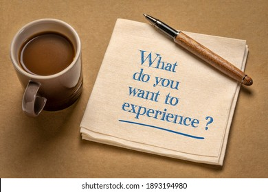 What do you want to experience? Inspirational question on a napkin with a cup of coffee. Planning and goal setting concept.