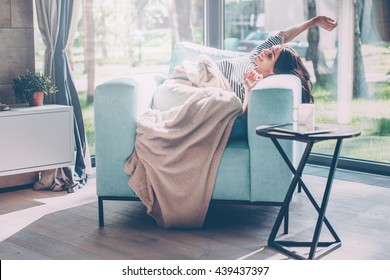 What a great morning! Beautiful young woman stretching out hands and smiling while lying in a big comfortable chair at home