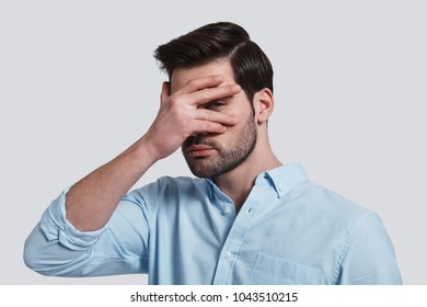 What is there?  Handsome young man covering eyes with hand and peeking while standing grey background
