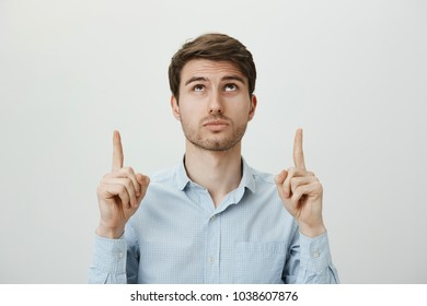 What is happening upstairs. Studio shot of curious and interested white good-looking unshaven male in blue shirt, pointing up with index fingers, looking at ceiling, wondering over gray wall
