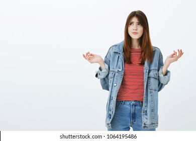 What the hell was that. Portrait of confused misunderstood good-looking girlfriend in denim jacket and striped blouse, spreading hands cluelessly, frowning and looking up unaware and questioned