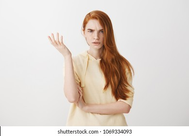 What the hell are you talking about, nonsense. Studio shot of frustrated female with red hair gesturing with raised palm, frowning, being displeased and confused with dumb question over gray wall