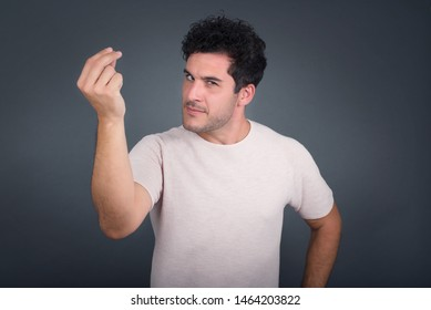 What the hell are you talking about. Shot of frustrated young European man gesturing with raised hand doing Italian gesture, frowning, being displeased and confused with dumb question.