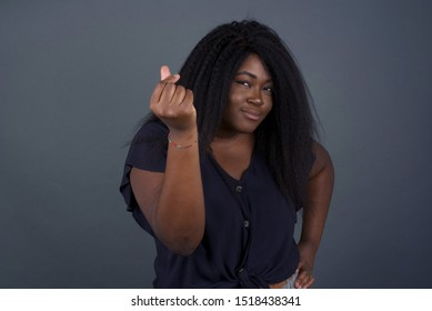 What the hell are you talking about. Shot of frustrated young African American woman gesturing with raised hand doing Italian gesture, frowning, being displeased and confused with dumb question.
