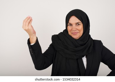 What the hell are you talking about. Shot of frustrated muslim woman gesturing with raised hand doing Italian gesture, frowning, being displeased and confused with dumb question.