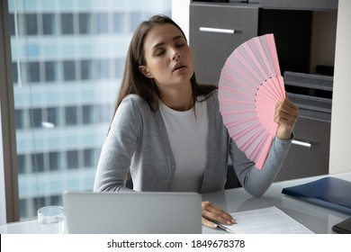 What a hot day! Exhausted millennial female office worker manager employee sitting at desk waving herself with hand fan suffering from summer heat too sultry air dreaming about conditioner humidifier