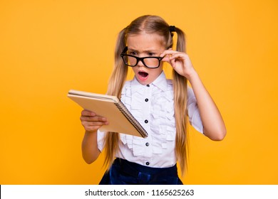 What is it! I do not understand it! Close up photo portrait of sad angry annoyed upset schoolkid with open mouth adjusting glasses staring looking at copybook textbook isolated bright background