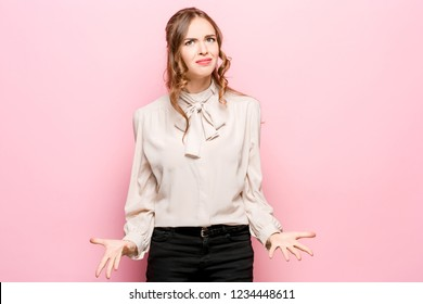 What is it. The female portrait isolated on pink studio backgroud. Anger. Young, emotional, angry, scared woman looking at camera. Human emotions, facial expression concept.