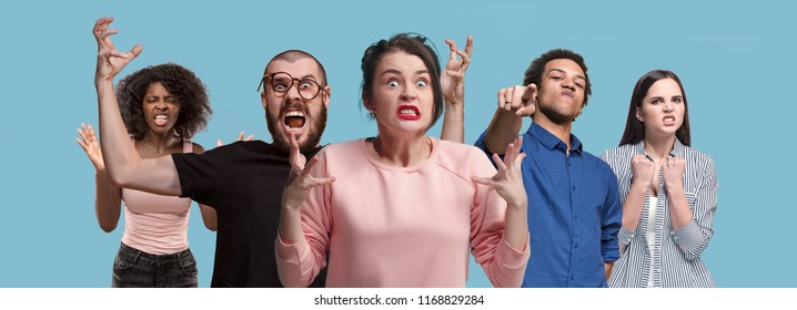 What is it. The male and female portrait isolated on blue studio backgroud. Anger. Young, emotional, angry, scared people looking at camera. Human emotions, facial expression concept. Trendy colors