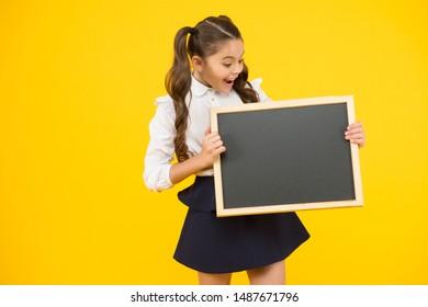 What is it. Surprised girl holding blackboard on yellow background. Little child preparing blackboard for lesson. Small kid with school blackboard. Blank blackboard for school advert, copy space.