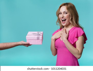 What lovely present. Waist up portrait of joyful girl receiving present box in male hand. She is laughing and looking at camera with excitement. Isolated
