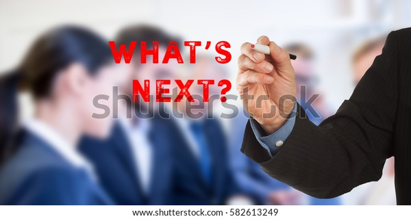 What is next? Male hand in business wear holding a thick pen, writing on an imaginary screen at the camera, business team in background, digital composing.
