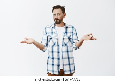 So what is our problem. Confused and puzzled handsome mature caucasian man with beard and moustache, standing with spread hands in clueless pose, feeling questioned, cannot understand what happening