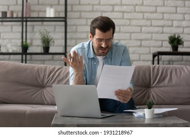 What an outrage. Annoyed young man sit on sofa work with papers at home office read mail letter with bad news unexpected debt. Anxious self employed guy worried by bank report having financial problem