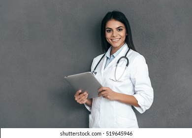 What seems to be a problem? Attractive young female doctor in white lab coat holding digital tablet and smiling while standing against grey background