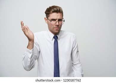 What is the problem?Studio shoot of young businessman showing misunderstanding,the absurdity of the situation, with stylish haircut, glasses,unshaved,dressed white shirt and blue tie, white background