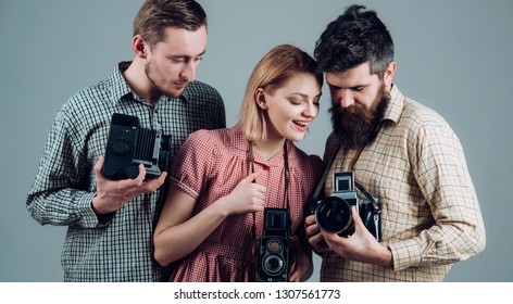 What a shot. Photography studio. Retro style woman and men hold analog photo cameras. Paparazzi or photojournalists with vintage old cameras. Group of photographers with retro cameras.