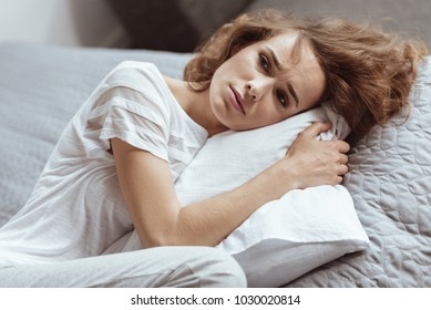 What should I do. Worried mature brunette lying on a pillow and thinking about something depressing at home.