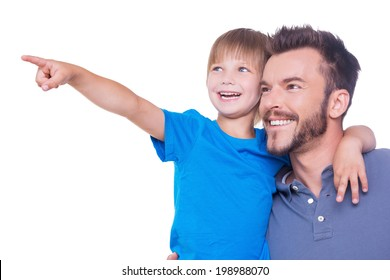What is there? Side view of happy father and son looking away while child pointing away and both standing isolated on white
