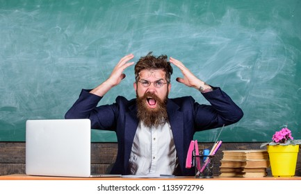 What stupid thought. Man bearded teacher aggressive expression sit classroom chalkboard background. Unpleasant wonder. Teacher wondered low level of knowledge. What are you talking about.