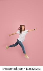 What is there interesting in the distance. seeking pretty happy young woman jumping and gesturing against pink studio background. Runnin girl in motion or movement. Human emotions and facial