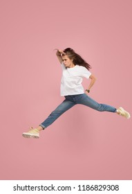 What is there interesting in the distance. seeking pretty happy young woman jumping and grabbing against pink studio background. Runnin girl in motion or movement. Human emotions and facial