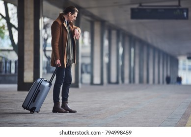 What time is it. Full length side view serious man looking at modern watch while keeping big suitcase. He waiting for train. Trip concept
