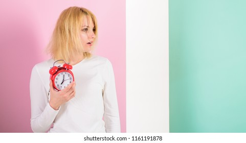 What time is it. Lack of sleep bad for health. Oversleeping side effects too much sleep harmful. Girl drowsy tousled hair just woke up holds alarm clock. Bad sleep habits effects on life, copy space.